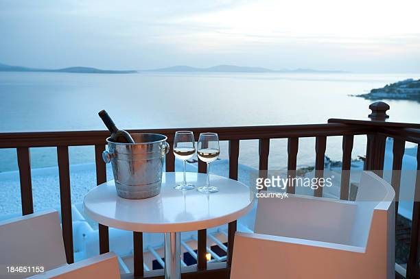 Two glasses of wine on a balcony at sunset
