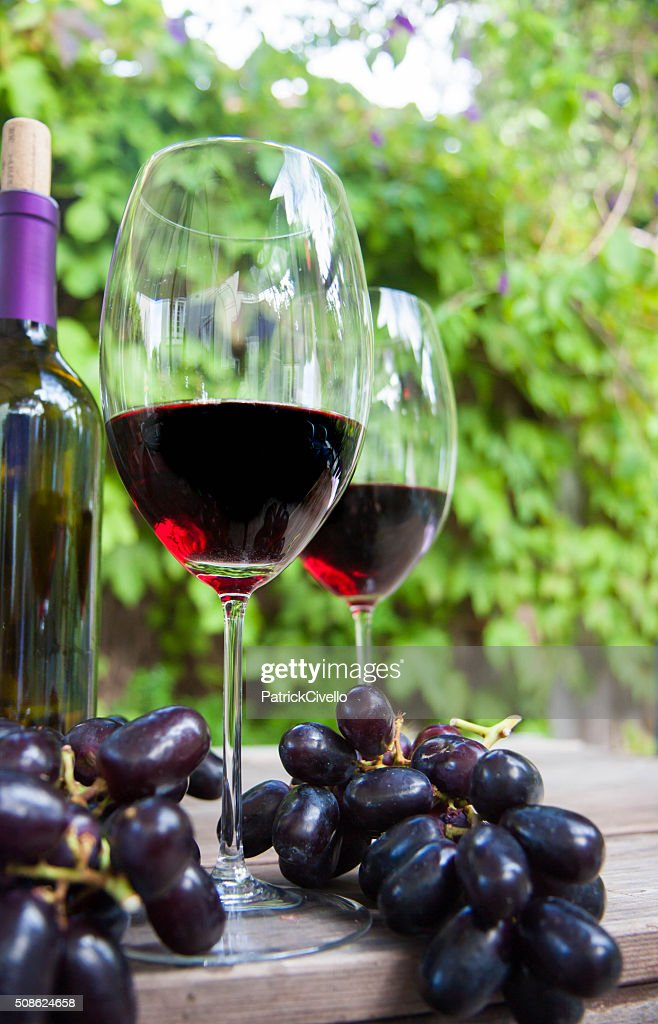 Two glasses red wine with bottle and grapes on table. : Stock Photo