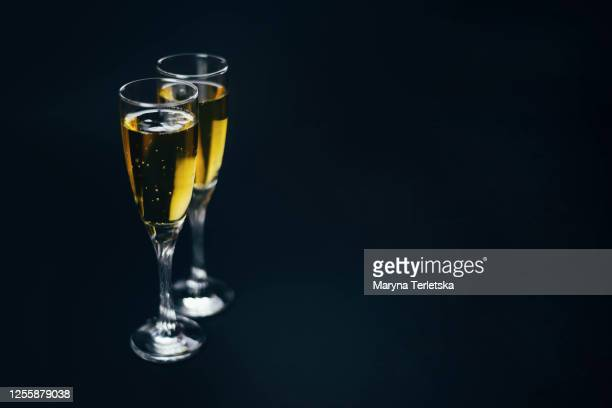 two glasses with champagne on a black background. - letra t imagens e fotografias de stock