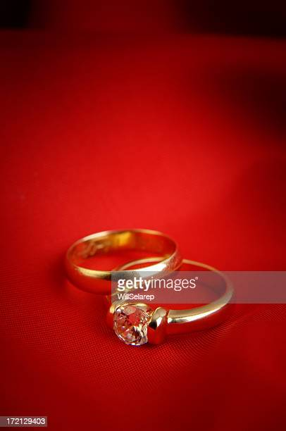 Two gold rings in red background