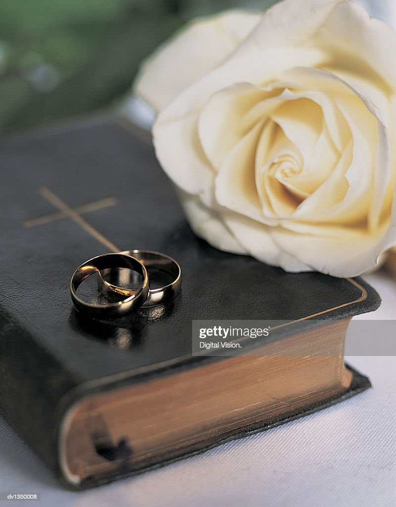 Two Gold Wedding Bands On A Bible With A Rose Stock Photo Getty