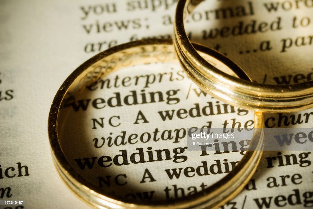 Two gold wedding bands on top of paper with the word wedding : Stock Photo