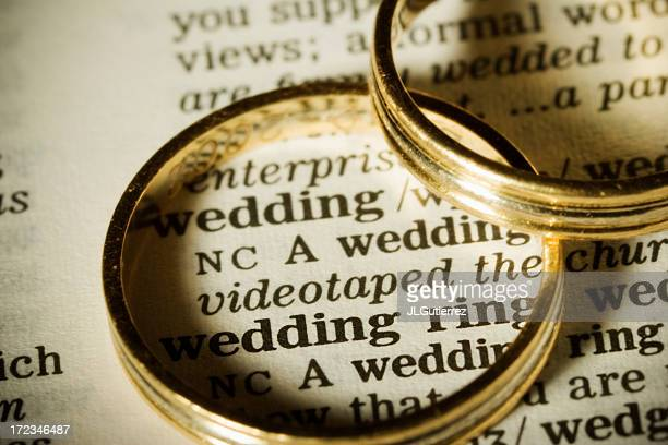 Two gold wedding bands on top of paper with the word wedding