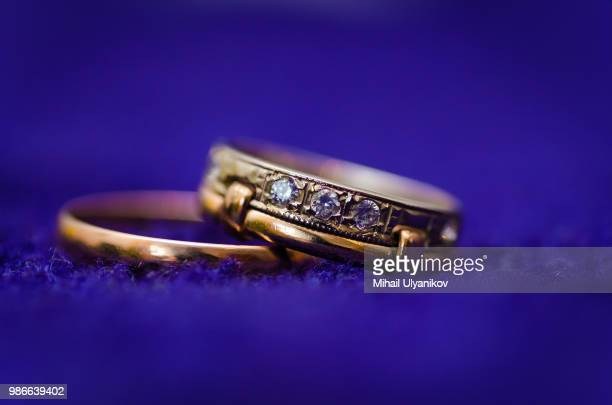 two gold wedding rings on dark background. macro photo - bringing home the bacon stock photos and pictures