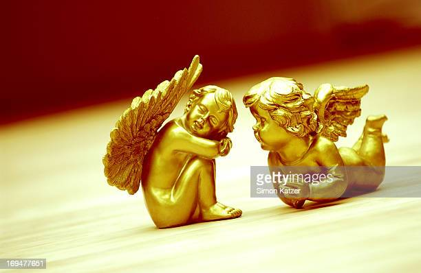 Two golden angels laying on the floor
