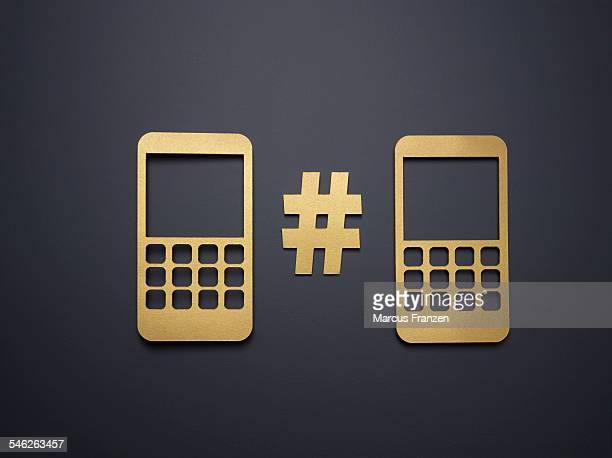Two golden paper phones on grey with a hashtag