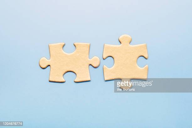 two golden puzzle pieces on blue background - teilabschnitt stock-fotos und bilder