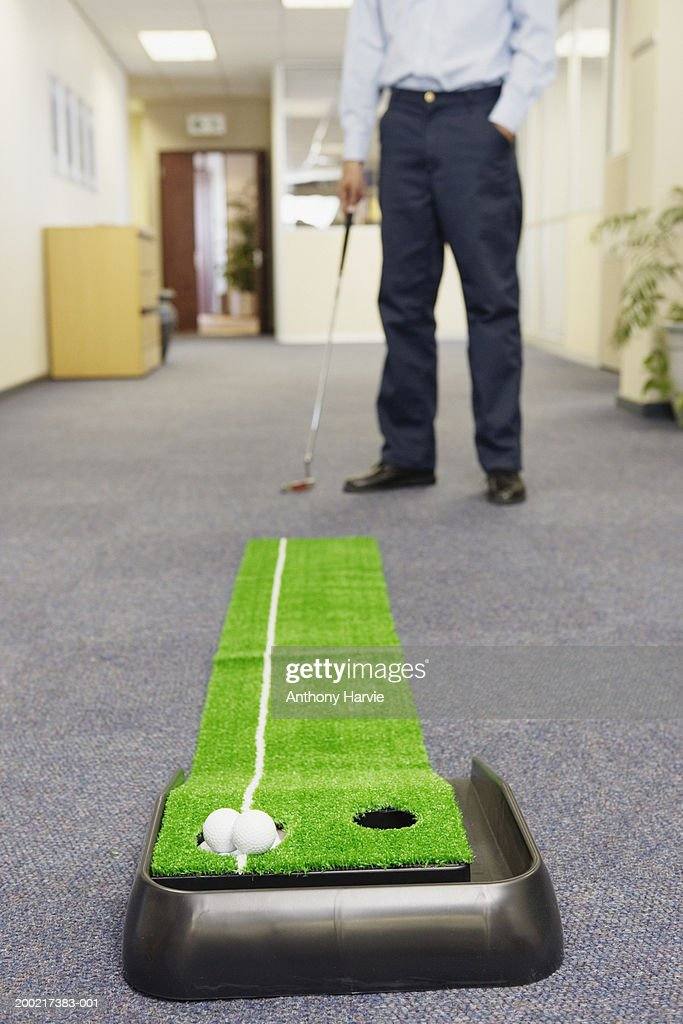 Two Golf Balls In Hole Of Indoor Golf Set Man Standing In Background ...