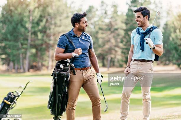 two golf players talking on the golf course - khaki trousers stock pictures, royalty-free photos & images