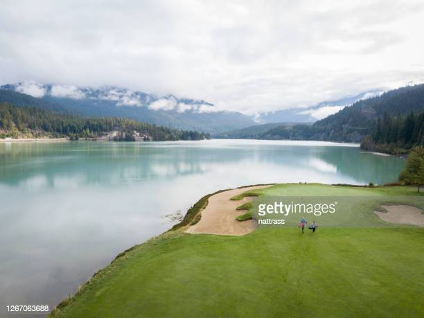 two golfers make their way towards the green - green golf course stock pictures, royalty-free photos & images