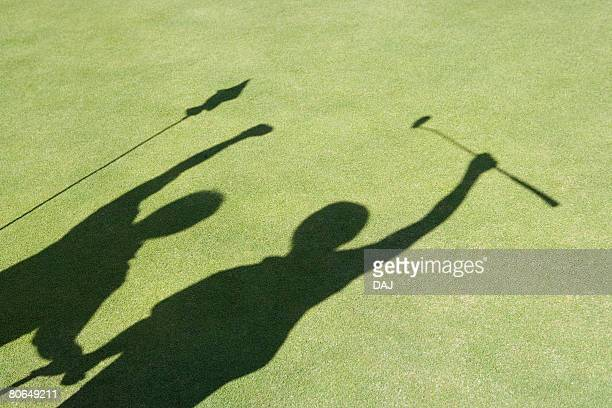 two golfers punching the air, green background, saipan, usa  - putting green stock pictures, royalty-free photos & images