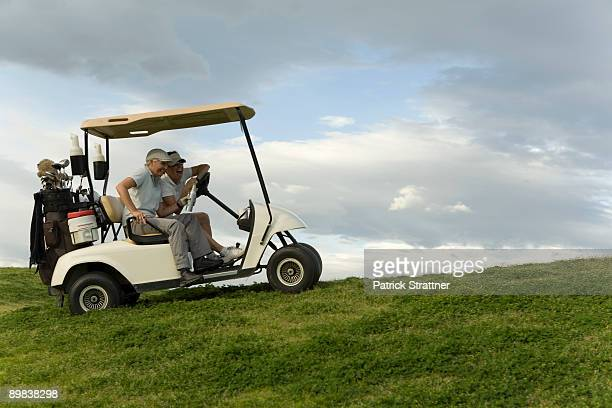 two golfers sitting in a golf cart and laughing - golf lustig stock-fotos und bilder