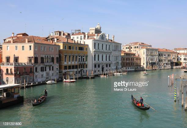 Two gondolas sail on the deserted Grand Canal during Carnival on February 16, 2021 in Venice, Italy. Venice is marking a second Carnival period...