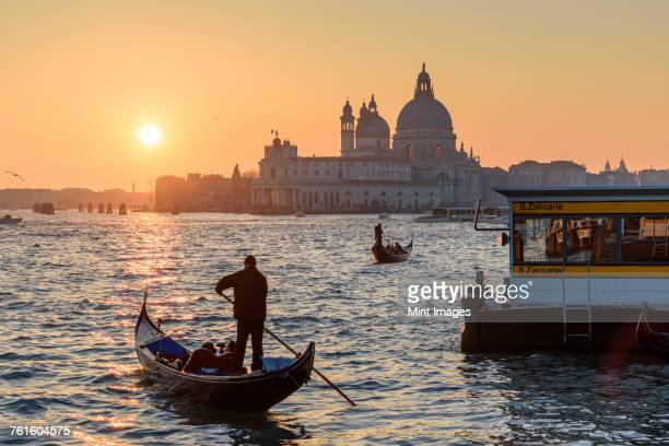 two gondoliers on the canale grande in venice, italy, at sunrise, with the dome of santa maria della salute in the distance. - gondola traditional boat stock pictures, royalty-free photos & images