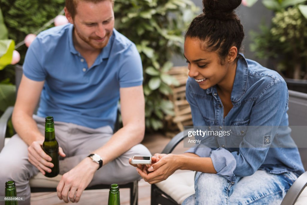Two good looking friends watching short videos on smartphone : Stock Photo