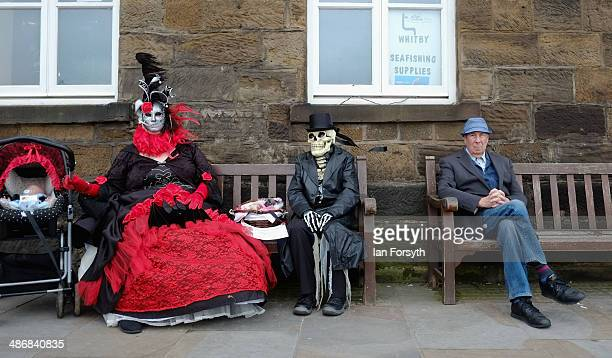Two goth women sit on a bench during the Goth weekend on April 26, 2014 in Whitby, England. The Whitby Goth weekend began in 1994 and happens twice...