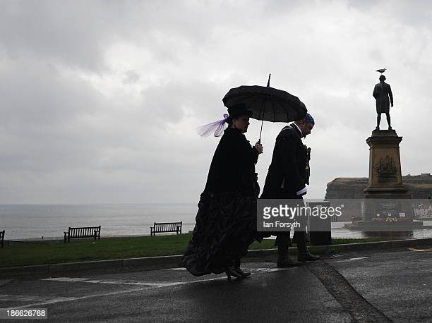 Two goths dressed in Victoriana style walk in the rain as they visit the Goth weekend on November 2 2013 in Whitby England The Whitby Gothic Weekend...