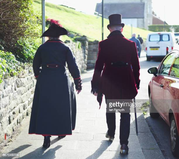 Two goths wearing Victoriana clothing walk through town during the Whitby Goth Weekend on October 27, 2017 in Whitby, England. The Whitby Goth...