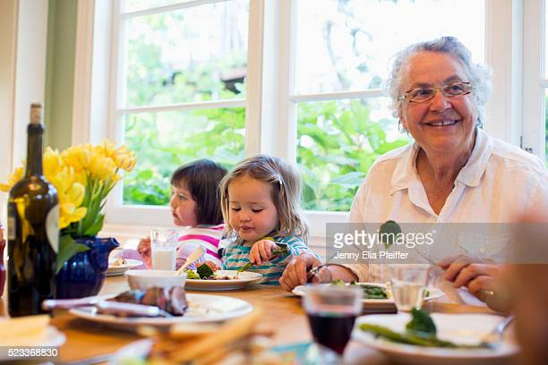 Two granddaughters (2-3, 4-5) eating dinner with grandma, California, USA