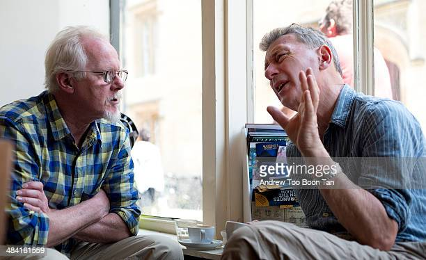 Two grandpas having a conversation by the window.