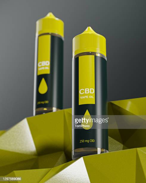 two green plastic tubes with yellow caps against gray background - cbd oil stock pictures, royalty-free photos & images