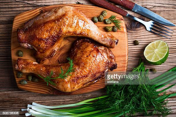 two grilled chicken legs, green onion, dill and lime on wooden board viewed from above - grelhado cozido - fotografias e filmes do acervo