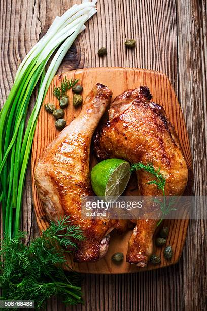 Two grilled chicken legs, green onion, dill and lime on wooden board viewed from above