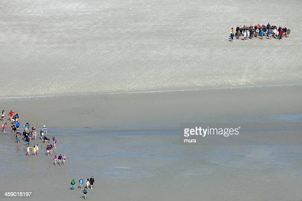 Two groups of tourists crossing the shore at St.Mont-Michel
