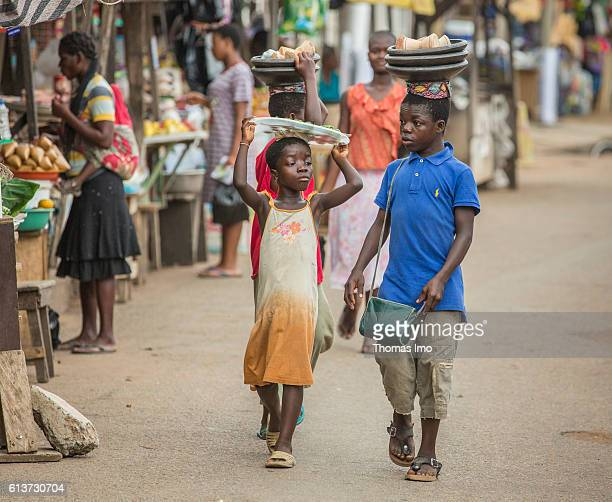 Two growthrestricted Africans transport their purchases on their heads at the market in Accra on September 08 2016 in Accra Ghana
