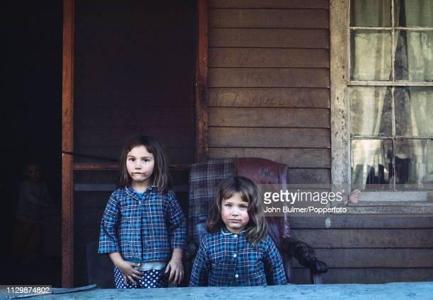 Two grubby girls outside a log house Pike County Kentucky US 1967