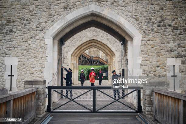 Two guards lower the Middle Drawbridge a ceremonial event to mark the reopening to the public of the Tower of London on July 10 2020 in London...
