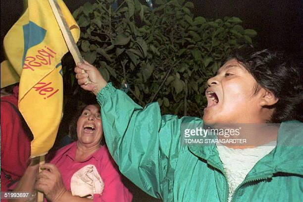 Two Guatemalan women celebrate the early lead of the National Vanguard Party PAN presidential candidate Alvaro Arzu 12 November in front of the PAN...