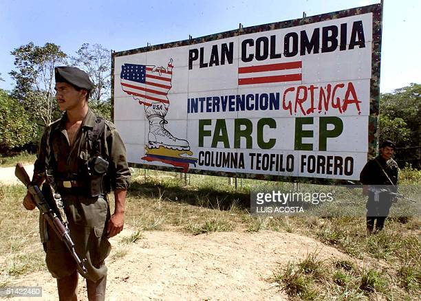 Two guerrillas of the Revolutionary Armed Forces of Colombia stand guard on a highway next to a billboard with propaganda against the USbacked...