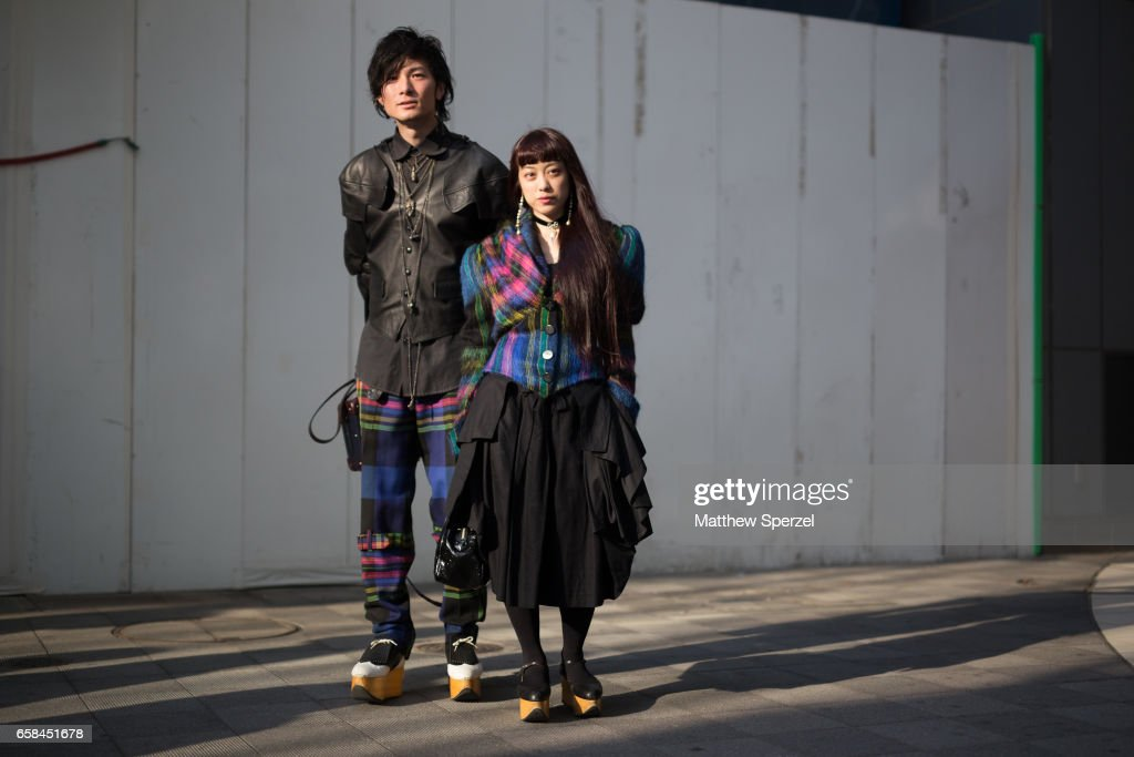 Two guests are seen on the street wearing black with multi-colored plaid outfits during Tokyo Fashion Week on March 25, 2017 in Tokyo, Japan.