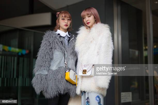Two guests are seen on the street wearing faux fur coats with white and yellow bags during Tokyo Fashion Week on March 20 2017 in Tokyo Japan