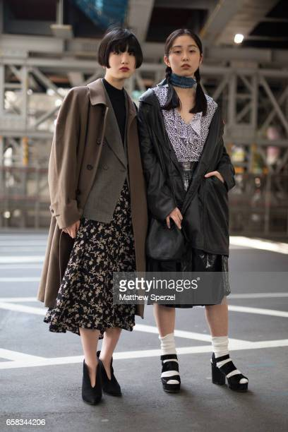 Two guests are seen on the street wearing long coats skirts and heels during Tokyo Fashion Week on March 20 2017 in Tokyo Japan