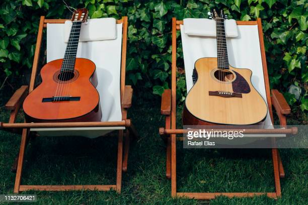 two guitars on two hammocks in the garden - duet stock pictures, royalty-free photos & images