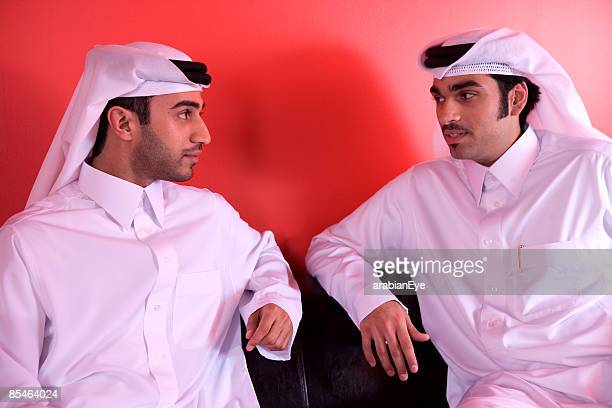 Two Gulf Arab men sitting together and having a conversation.