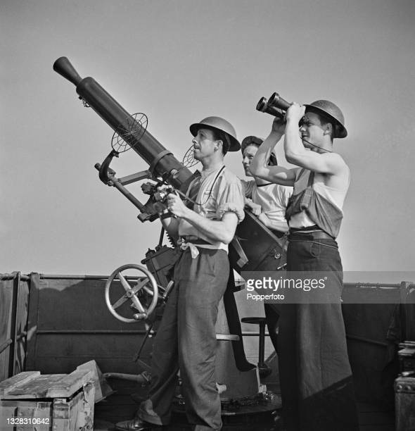 Two gun crew members and a photographer, standing next to a QF 2-pounder anti-aircraft gun, use naval binoculars to watch for enemy aircraft aboard...