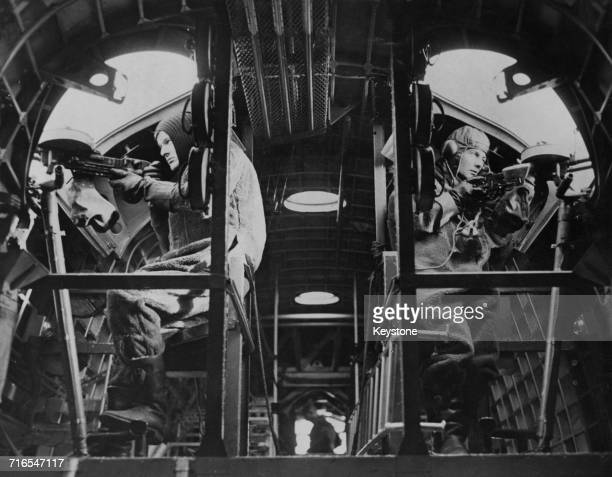 Two gunners in a Short Sunderland Mark I flying boat patrol bomber of No 210 Squadron RAF sit at their positions with 303 Vickers Ktype machine guns...