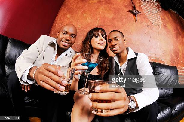 two guys and a girl holding drinks at a bar - groothoek stockfoto's en -beelden