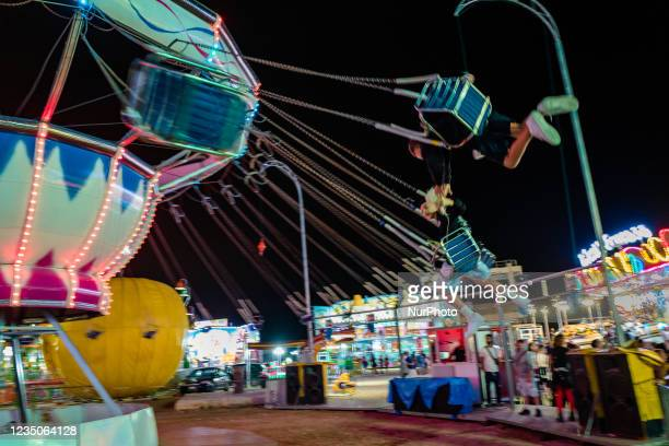 Two guys compete to catch the plume on the chain carousel, on the first day of the Luna Park opening in Molfetta on 4 September 2021. On the occasion...
