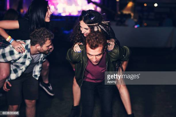Two guys giving a piggyback to their girlfriends at the music festival