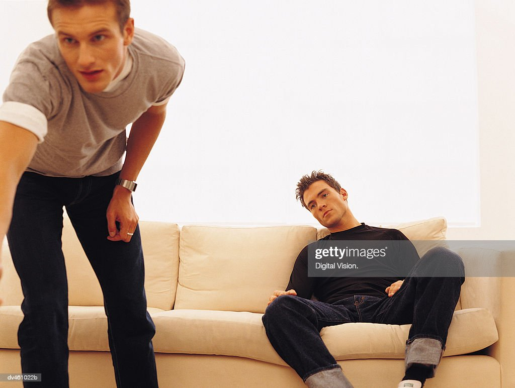 Two guys hanging out, one turning on television : Stock Photo