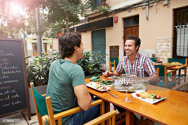 two guys having tapas at restaurant - klaus vedfelt mallorca stock pictures, royalty-free photos & images