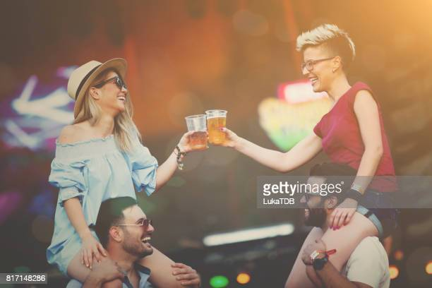 Two guys holding girls on arms on festival