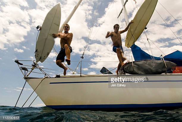 Two guys jumping off their boat heading out for surf in Costa Rica