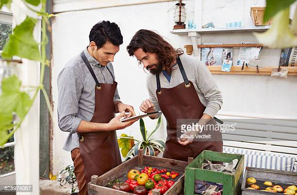 Two guys keeping track of produce with tablet