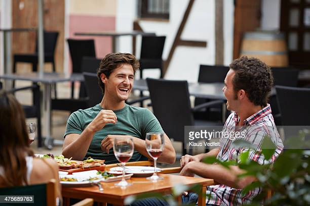 two guys lauging together at restaurant - klaus vedfelt mallorca stock pictures, royalty-free photos & images