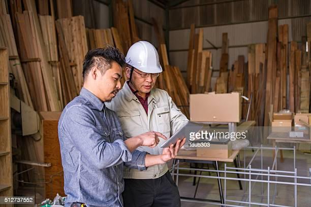 2 つの男性を見ているタブレットでは、産業用の環境